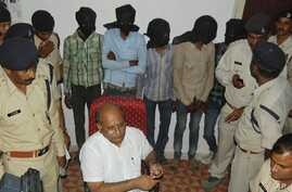 Five men, faces covered, are among the six accused of raping a Swiss tourist in central India, at police control room in Datia, March 17, 2013.