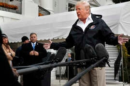 President Donald Trump answers questions from members of the media as he leaves the White House, Saturday Nov. 17, 2018, in Washington, en route to see fire damage in California. At far left is White House press secretary Sarah Huckabee Sanders.