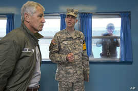 U.S. Secretary of Defense Chuck Hagel, left, listens to U.S. Army Col. James Minnich, as a North Korean soldier takes a photograph of the secretary through a window at a UN truce village building that sits on the border of the Demilitarized Zone (DMZ