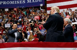 Singer Lee Greenwood points at President Donald Trump and Vice President Mike Pence as he sings during a campaign rally, Sunday, Nov. 4, 2018, in Chattanooga, Tenn.