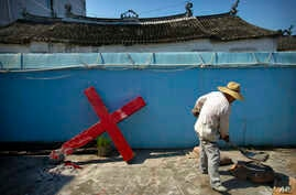 FILE - A church member shovels cement mix preparing to re-mount a cross on a Protestant church, which had been forcibly pulled down by Chinese government workers in Taitou Village, eastern China, July 29, 2015.