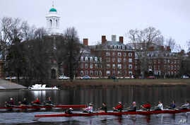 FILE - Rowers pass the campus of Harvard University as they move down the Charles River in Cambridge, Mass., March 7, 2017.  Harvard and the group Students for Fair Admissions will go to trial in a lawsuit alleging discrimination against Asian-Americ