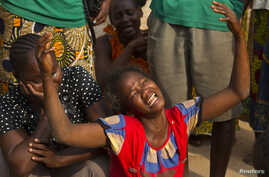 A woman reacts near the dead body of her sister who was killed during one of the latest incidents of sectarian violence in the 5th Arrondissement of the capital Bangui February 9, 2014. REUTERS/Siegfried Modola