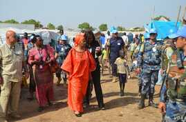 The executive director of UN Women, Phumzile Mlambo-Ngcuka (third from left) is briefed as she tours a U.N. base in Juba where thousands of people have sought shelter from weeks of unrest in South Sudan.