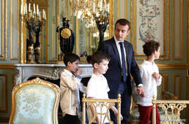 French President Emmanuel Macron holds the hand of a boy with autism as they visit the Elysee Palace before the launching of a program to enhance the diagnosis and treatment of autism, in Paris, July 6, 2017.