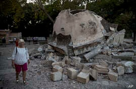 A tourist walks past a damaged structure outside a mosque after an earthquake at the Greek island of Kos, July 22, 2017.