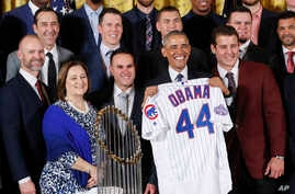 President Barack Obama holds up a personalized Chicago Cubs baseball jersey presented to him  during a ceremony in the East Room of the White House, Monday, Jan. 16, 2017, where the president honored the 2016 World Series champions.