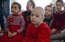 Lyuba, center, wearing a red outfit, sits along with other girls in a children's home in Khartsyzk, Ukraine, March 7, 2015.