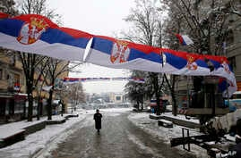 FILE - Workers hang Serbian flags in the northern, Serb-dominated part of ethnically divided town of Mitrovica, Kosovo, Dec. 14, 2018.