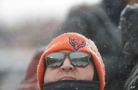 A Chicago Bears fan watches in the snow during an NFL football game against the Cleveland Browns in Chicago, Dec. 24, 2017.