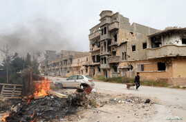 A man pulls a wheelbarrow past destroyed buildings after clashes between military forces loyal to Libya's eastern government and Islamist fighters, in Benghazi, Libya, Feb. 28, 2016.