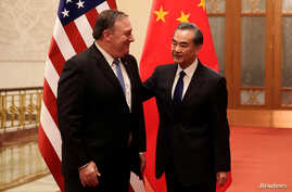 U.S. Secretary of State Mike Pompeo chats with Chinese Foreign Minister Wang Yi before their meeting at the Great Hall of the People in Beijing, China, June 14, 2018.