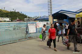 Stranded passengers leave the port after learning that ferry services were stopped in preparation for an approaching storm in Marinduque island, central Philippines, April 4, 2015.