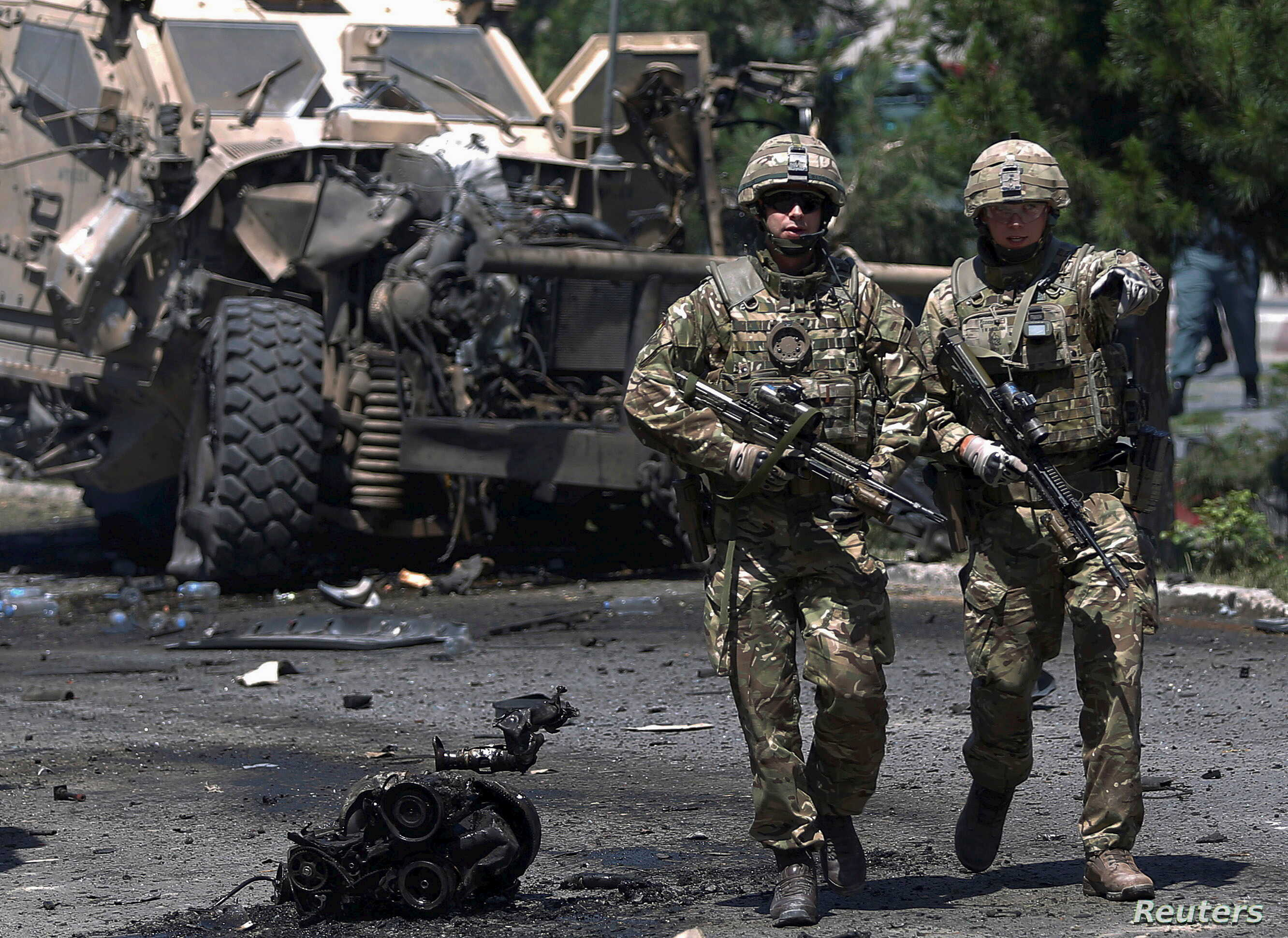 NATO soldiers walk at the site of a suicide bomb attack in Kabul, Afghanistan, June 30, 2015.