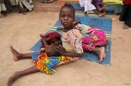A girl rescued from the Sambisa forest cradles another girl in her lap at a displaced persons camp in Malkohi, Nigeria on May 5, 2015. (Chris Stein/VOA)