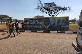 Members of ZANU-PF walk past their party's poster at a rally (07/28/2018) in Harare with promises for jobs if President Mnangagwa wins July elections, July 28, 2018.