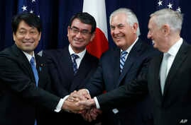 """From left, Japanese Defense Minister Itsunori Onodera, Japanese Foreign Minister Taro Kono, Secretary of State Rex Tillerson and Defense Secretary James Mattis shake hands """"ASEAN style"""" at the start of a Security Consultative Committee meeting at the..."""