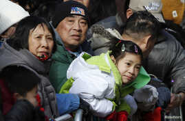 FILE - People watch the 14th Annual Chinatown Lunar New Year Parade in New York.