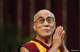 FILE - The Dalai Lama gestures before speaking to students during a talk at Mumbai University.