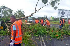 Road workers remove a fallen tree blocking a road near Lami, Fiji, Feb. 21, 2016, after cyclone Winston ripped through the country. Officials in Fiji are assessing damage in the wake of the ferocious cyclone that tore through the Pacific island chain