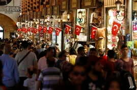 People walk in a covered market in Istanbul, Turkey, Aug. 20, 2018. Tourists have returned in droves to Turkey according to government figures, helped this summer by the sharp fall in the value of the Turkish lira.