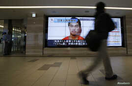 A man walks past screens displaying a television news programme showing an image of Kenji Goto, one of two Japanese citizens taken captive by Islamic State militants, on a street in Tokyo, January 25, 2015.