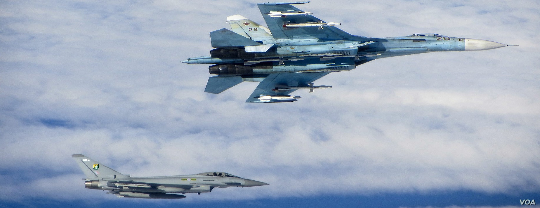 A Russian SU-27 Flanker aircraft banks away with a RAF Typhoon in the background. RAF Typhoons were scrambled on June 17 to intercept multiple Russian aircraft in international airspace as part of NATO's ongoing Baltic Air Policing Mission. (UK Minis