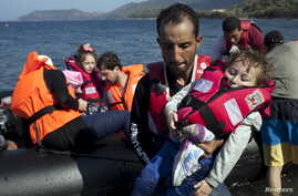 A Syrian refugee holds a baby moments after arriving on a dinghy on the Greek island of Lesbos, Sept. 11, 2015.