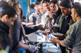 FILE - People receive food in a tent camp for refugees and migrants in Brussels, Sept. 10, 2015.