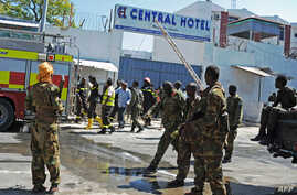 Somali security forces, paramedics and firefighters stand outside the Central Hotel, close to the presidential palace, in Mogadishu, Feb. 20, 2015.