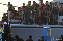 Migrants are seen onboard an Italian Coast Guard vessel following a rescue operation at the port on the Greek island of Kos, Aug. 16, 2015.