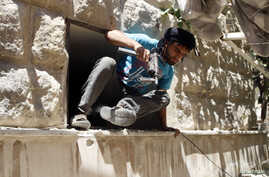 A Free Syrian Army fighter climbs through a hole in a wall in Bustan al-Basha district in Aleppo, Syria, May 19, 2014.
