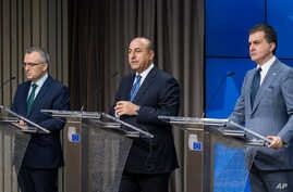 Turkey's EU Affairs Minister Omer Celik, right, Foreign Minister Mevlut Cavusoglu, center, and Finance Minister Agbal Nihat address the media after an EU Turkey Accession Intergovernmental Conference at the EU Council building in Brussels, June 30, 2...