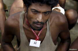 An identity number tag is seen on the neck of a migrant, who was found at sea on a boat, near Kanyin Chaung jetty after landing outside Maungdaw township, northern Rakhine state, Myanmar, June 3, 2015.