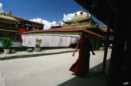 A Tibetan monk walks along the halls of the Jokhang Buddhist temple in Lhasa, Tibet, July 5, 2006.