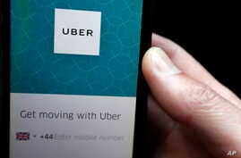 FILE - An Uber app is displayed on a phone in London, Sept. 22, 2017.