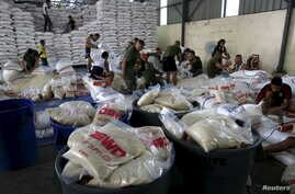Members of the Armed Forces of the Philippines help out volunteers repacking food rations for victims of Typhoon Noul at the Department of Social Welfare Development (DSWD) headquarters in Pasay city, south of Manila, May 9, 2015.