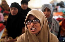 Nurshardrina Khairadhinia, 19, from Indonesia, the cousin of a young man suspected of being a member of so-called Islamic State (IS), speaks during an interview with the Associated Press, inside their tent at a refugee camp, in Ain Issa, Syria; July