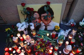 Candles sit in front of a photo of journalist Jan Kuciak and his fiancee during a rally to mark one year anniversary of the slayings of Kuciak and his fiancee, in Bratislava, Slovakia, Feb. 21, 2019.