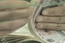 A bank teller counts a stack of US and Chinese currency.
