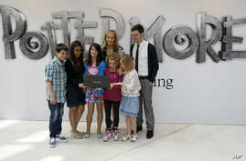 [÷/ُ - British author J.K. Rowling, centre back, poses for photographers with participants during a photo call for her new website project Pottermore at the Victoria and Albert Museum in London, Thursday, June 23, 2011.