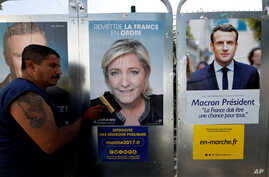 Campaign posters of French National Front (FN) political party leader Marine Le Pen (C) and head of the political movement En Marche! (Onwards!) Emmanuel Macron (R), are seen in Antibes, France, April 14, 2017.