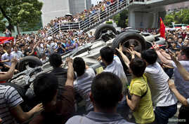 Protesters overturn a Japanese-brand police car during an anti-Japan protest in Shenzhen, Guangdong province, August 19, 2012.