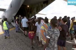 In this image made from video March 21, 2019, storm evacuees board an Australian Defense Force C-130 plane preparing in Borroloola, Australia, before the arrive of two powerful cyclones on Australia's sparsely populated north where about 2,000 people...