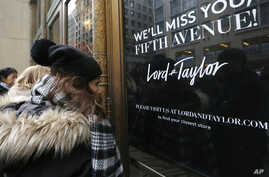 Women peer in the front door of Lord & Taylor's flagship Fifth Avenue store which closed for good, Jan. 2, 2019, in New York.