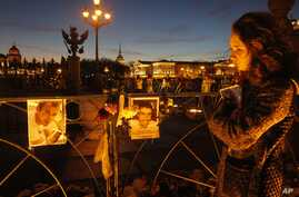 A woman reacts standing at pictures of the plane crash victims are attached to the fence at Dvortsovaya (Palace) Square in St.Petersburg, Russia, Nov. 3, 2015.