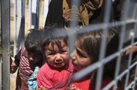 A Syrian child carries a baby crying while they wait with others to cross back to the border town of Tal Abyad in Syria from Turkey, at the border crossing in Akcakale, southeastern Turkey, Wednesday, June 17, 2015.  Some hundreds of Syrians are retu