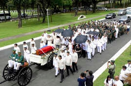 In this photo provided by the Office of Ilocos Norte Governor Imee Marcos, Imelda Marcos, in black on a wheelchair under an umbrella, the widow of the late dictator Ferdinand Marcos, and their close relatives follow the flag-draped casket of Ferdinan
