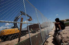 A child looks at U.S. workers building a section of the U.S.-Mexico border wall at Sunland Park, U.S. opposite the Mexican border city of Ciudad Juarez, Mexico, Aug. 26, 2016. Picture taken from the Mexico side of the U.S.-Mexico border.