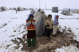 Internally displaced Afghan children stand outside their shelter in the cold at a refugee camp on the outskirts of Herat city January 20, 2015. REUTERS/ Mohammad Shoib (AFGHANISTAN - Tags: SOCIETY ENVIRONMENT TPX IMAGES OF THE DAY) - RTR4M4RK